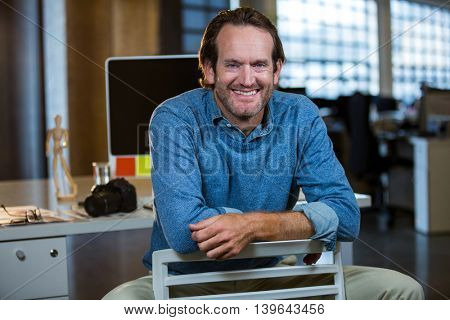 Portrait of creative businessman sitting on chair against computer desk in office