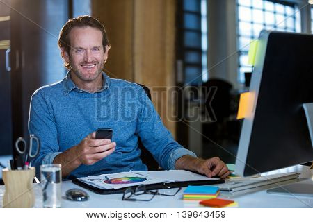 Portrait of happy businessman with cellphone at computer desk in office