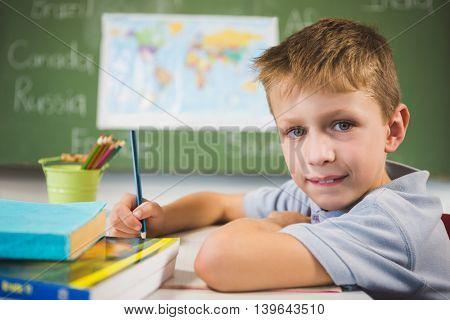 Portrait of schoolboy doing homework in classroom at school