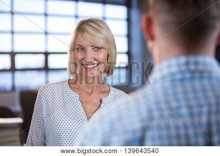 Happy creative businesswoman standing in front of male colleague in office