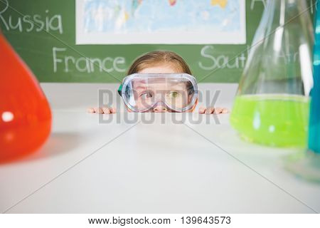 Schoolgirl doing a chemical experiment in laboratory at school