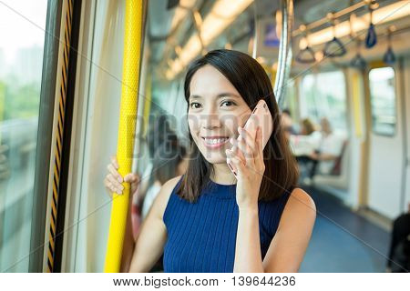 Woman talk to mobile phone inside train compartment