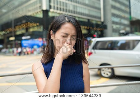Woman feeling nose allergy at outdoor