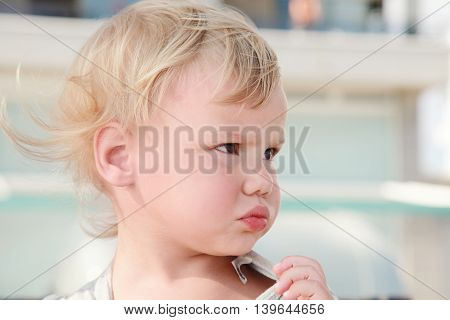 Outdoor Close Up Portrait Of Confused Blond Baby Girl