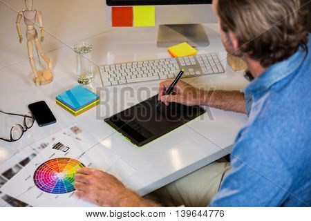 High angle view of businessman using graphics tablet at desk in creative office