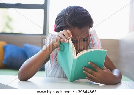 Schoolgirl reading book in library at school