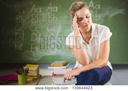 Tensed school teacher sitting with hand on forehead in classroom at school