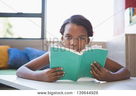 Portrait of schoolgirl reading book in library at school