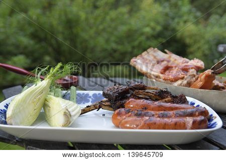 Close-up of a plate with fennel and sausages and ribs and in the background a pincers grabbing a chicken breast.