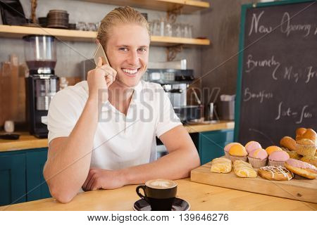 Waiter talking on mobile phone in cafeteria
