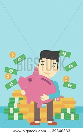 An asian happy young businessman holding a big piggy bank in hands under money rain on the background of stacks of gold coins. Vector flat design illustration. Vertical layout.