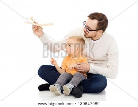 family, childhood, fatherhood, leisure and people concept - happy father and little son playing with toy airplane