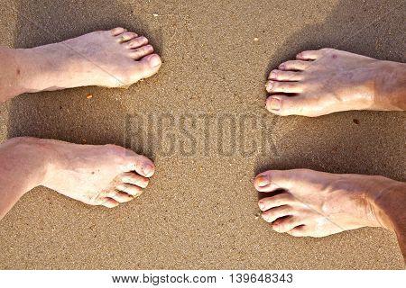 Feet Of A Couple At The Beach