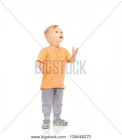childhood, emotion, expression and people concept - happy little boy in casual clothes looking up at something