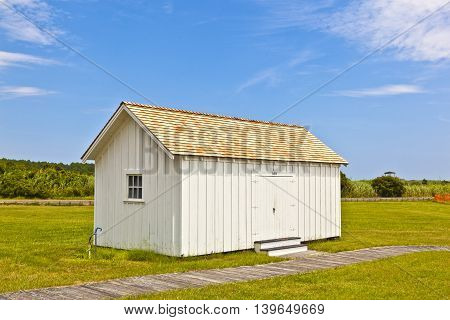 Hut at Bodie Island Lighthouse under blue sky