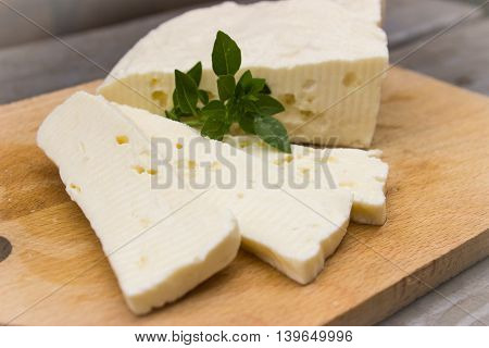 Homemade cheese and basil on  wooden background