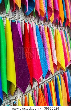 Multi-colored towels hung on the wall with pegs.
