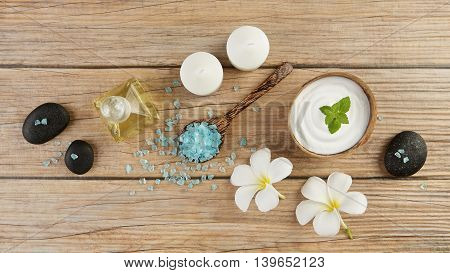 Spa Setting Concept With Oil Bottle, Blue Salt Sea In Spoon, Mint On Top Of White Cream In Coconut S