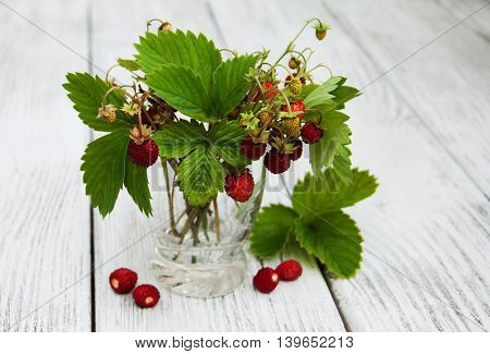 Glass with wild strawberries on a wooden table