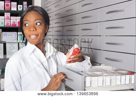 Young and black pharmacist at medicine cabinet