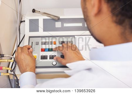 Male interracial otolaryngologist on hearing test machine