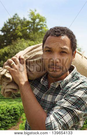 Brazilian coffee farmer at coffee plantation with coffee sack