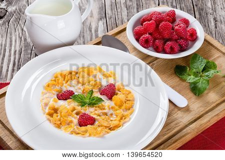 crispy corn flakes with raspberry and milk in plate decorated with mint on wooden worktop jug with milk and bowl with raspberry on cutting board close-up