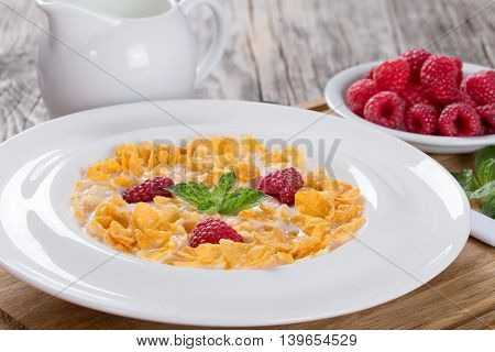 crispy corn flakes with raspberry and milk in plate decorated with mint on wooden worktop traditional and quick breakfast close-up