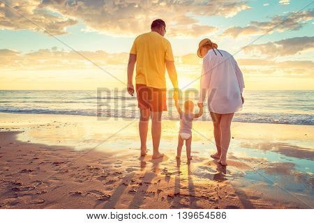 Grandfather and grandmother with grandson holding hands of each other on the beach at susnet. Color-toning applied.