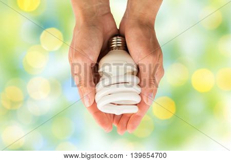 recycling, electricity, environment and ecology concept - close up of hands holding energy saving lightbulb or lamp over green lights background