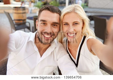 love, date, technology, people and relations concept - smiling happy couple taking selfie at restaurant terrace