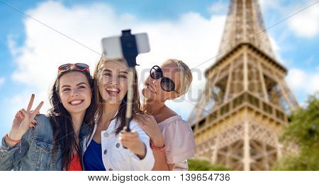 summer vacation, holidays, travel, technology and people concept- group of smiling young women taking picture with smartphone on selfie stick over eiffel tower in paris background