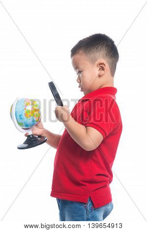 Portrait asian child holding earth globe map in his hand looking through magnifying loupe