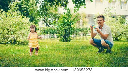 Dad and his daughter are making bubbles in the park. Colorful panoram image for modern lifestyle family concept.