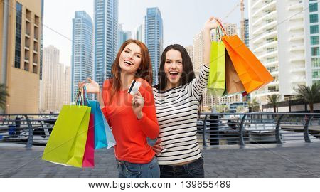 shopping, sale, tourism and people concept - two smiling teenage girls with shopping bags and credit card over dubai city skyscrapers background