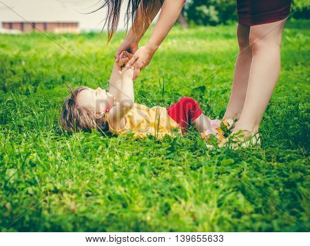 Mother and little daughter playing together on grass in park