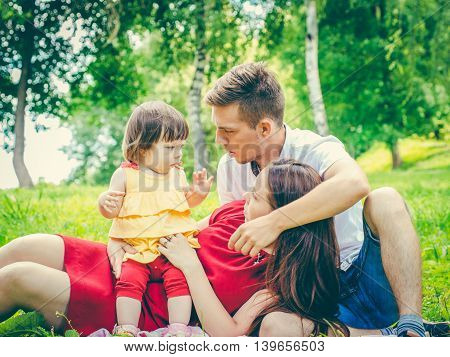 naughty little baby and parents with tired and discontented expression. Parents tired of baby concept