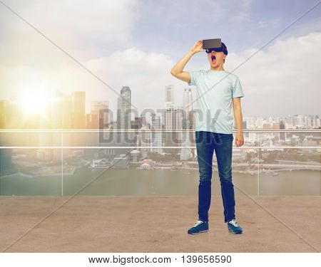 3d technology, virtual reality, entertainment, cyberspace and people concept - amazed man with virtual reality headset or 3d glasses looking at something over singapore city skyscrapers background