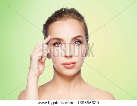 beauty, people and plastic surgery concept - beautiful young woman showing her forehead over green background