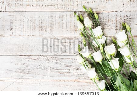 Old white wooden background with bouquet of white flowers. Mother's and Valentine's day concept with copy space for text.