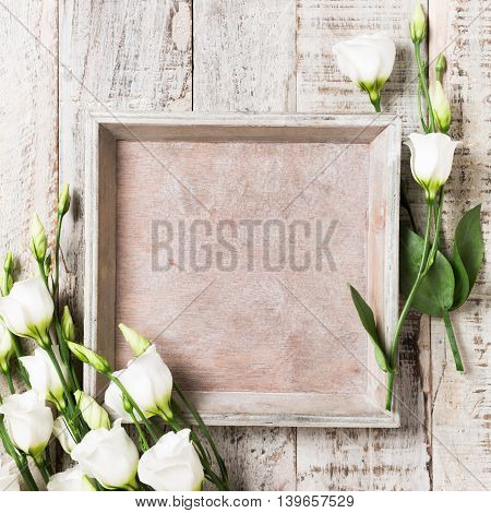 Old white wooden background with bouquet of white flowers and square tray. Mother's and Valentine's day concept with copy space for text.