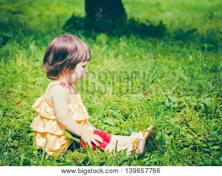 One year old baby girl sitting on grass and looking away. Colorful image with copy space