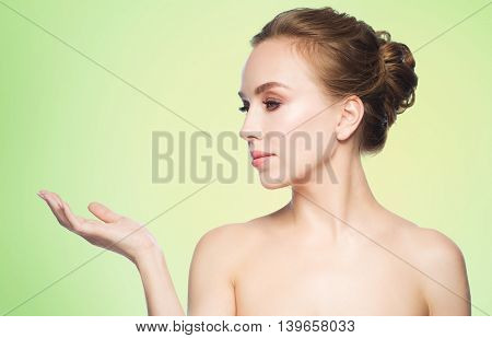 beauty, people, advertisement and health concept - smiling young woman holding something on palm of her hand over green background