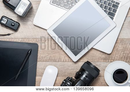 Concept of photographer work station. Top view of diverse personal equipment for photographer laying on the wooden grain