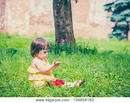 One year old baby girl sitting on grass and looking at his hand. Colorful image with copy space
