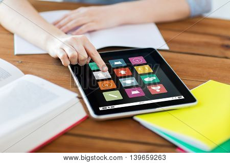business, education, technology and multimedia concept - close up of student woman with menu icons on tablet pc computer screen and notebook at home