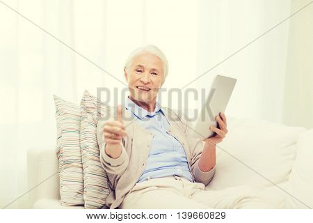 technology, age, gesture and people concept - happy senior woman with tablet pc computer showing thumbs up at home