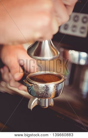 Hands holding tamper with coffee powder in cafeteria