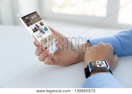 business, technology, media, internet and people concept - close up of woman hand holding and showing transparent smart phone with blog web page on screen and watch at office