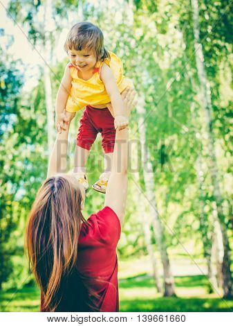Mother and his little one-year old daughter having fun. Mother throws up his little girl. Colorful image for modern life family concept